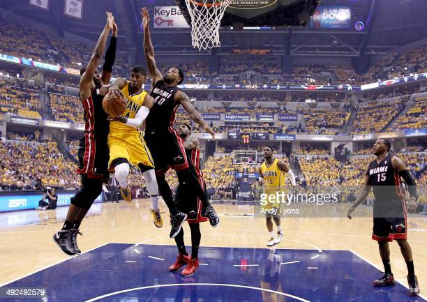 Paul George of the Indiana Pacers drives to the basket against Chris Bosh and Udonis Haslem of the Miami Heat during Game Two of the Eastern...