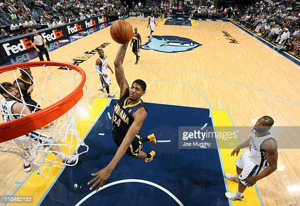 Paul George of the Indiana Pacers dunks against Sam Young of the Memphis Grizzlies on March 19 2011 at FedExForum in Memphis Tennessee NOTE TO USER...
