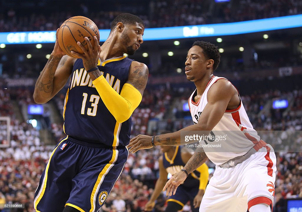 Paul George #13 of the Indiana Pacers holds on to the ball as he is watched by DeMar DeRozan #10 of Toronto Raptors in Game One of the Eastern Conference Quarterfinals during the 2016 NBA Playoffs on April 16, 2016 at the Air Canada Centre in Toronto, Ontario, Canada.