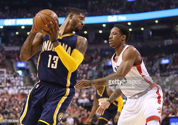 Paul George of the Indiana Pacers holds on to the ball as he is watched by DeMar DeRozan of Toronto Raptors in Game One of the Eastern Conference...
