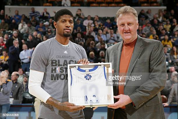 Paul George of the Indiana Pacers is handed his All Star Jersey from former NBA player Larry Bird before the game against the Charlotte Hornets on...