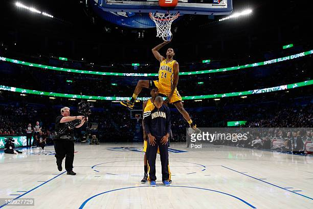 Paul George of the Indiana Pacers jumps over pacers teammates Roy Hibbert and Dahntay Jones as he dunks during the Sprite Slam Dunk Contest part of...