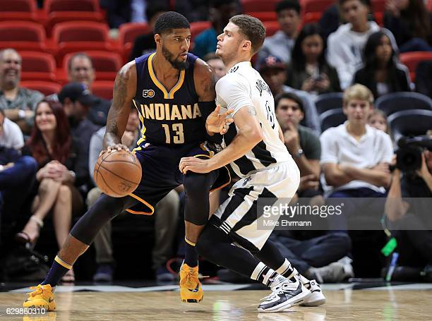Paul George of the Indiana Pacers posts up Tyler Johnson of the Miami Heat during a game at American Airlines Arena on December 14 2016 in Miami...