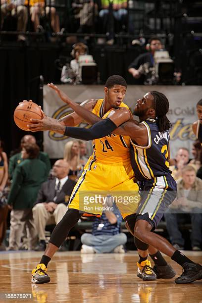 Paul George of the Indiana Pacers protects the ball from DeMarre Carroll of the Utah Jazz during the game between the Indiana Pacers and the Utah...