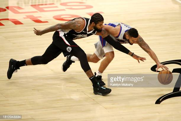 Paul George of the Los Angeles Clippers and Cory Joseph of the Detroit Pistons dive for the ball during the third quarter at Staples Center on April...