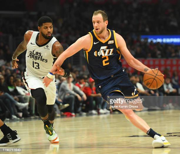 Paul George of the Los Angeles Clippers guards Joe Ingles of the Utah Jazz as he drives to the basket in the second half of the game at Staples...