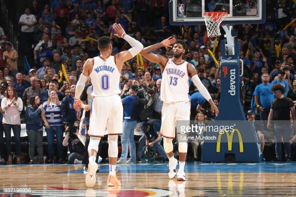 Paul George of the Oklahoma City Thunder and Russell Westbrook of the Oklahoma City Thunder high five during the game against the Miami Heat on March...