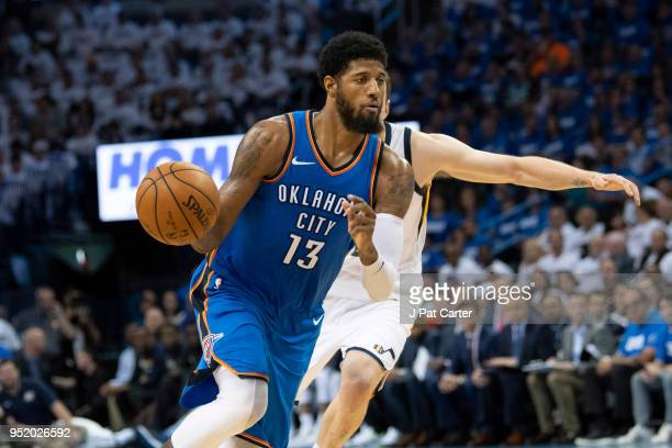 Paul George of the Oklahoma City Thunder brings the ball up court as Joe Ingles of the Utah Jazz applies pressure during game 5 of the Western...