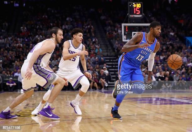 Paul George of the Oklahoma City Thunder dribbles past Kosta Koufos and Justin Jackson of the Sacramento Kings at Golden 1 Center on November 7 2017...