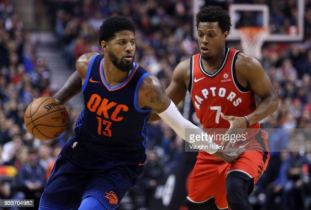 Paul George of the Oklahoma City Thunder dribbles the ball as Kyle Lowry of the Toronto Raptors defends during the first half of an NBA game at Air...