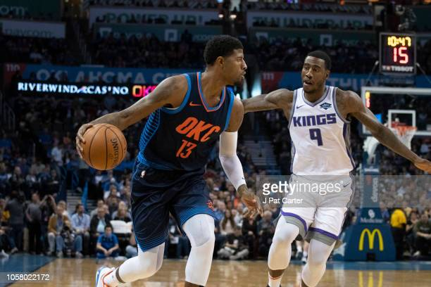Paul George of the Oklahoma City Thunder drives around Iman Shumpert of the Sacramento Kings during the first half of a NBA game at the Chesapeake...