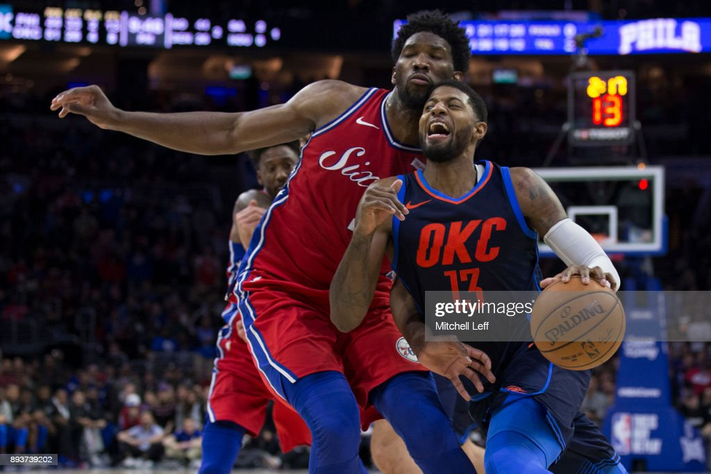 Paul George #13 of the Oklahoma City Thunder drives to the basket against Joel Embiid #21 of the Philadelphia 76ers in double overtime at the Wells Fargo Center on December 15, 2017 in Philadelphia, Pennsylvania. The Thunder defeated the 76ers 119-117 in triple overtime.