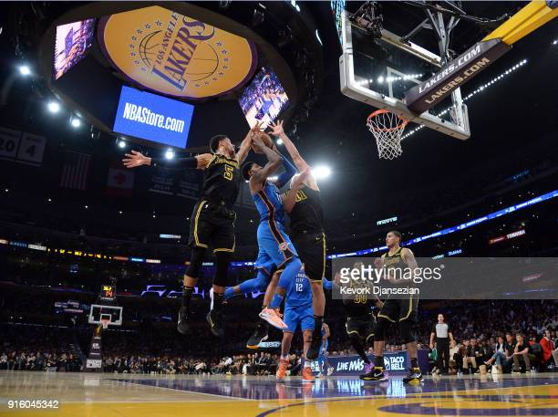 Paul George of the Oklahoma City Thunder drives to the basket against Josh Hart and Brook Lopez of the Los Angeles Lakers during the first half of a...