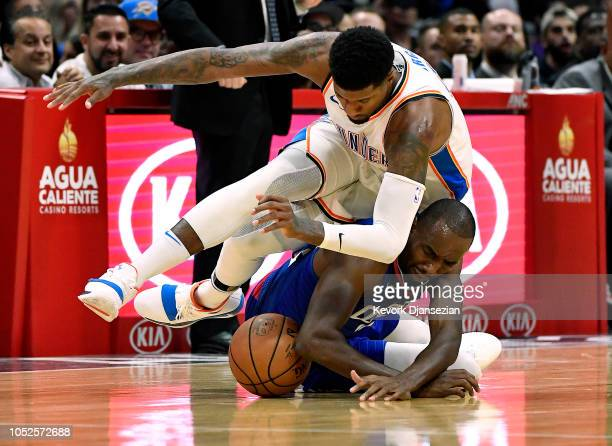 Paul George of the Oklahoma City Thunder falls on top of Luc Mbah a Moute of the Los Angeles Clippers as they battle for the ball during the second...