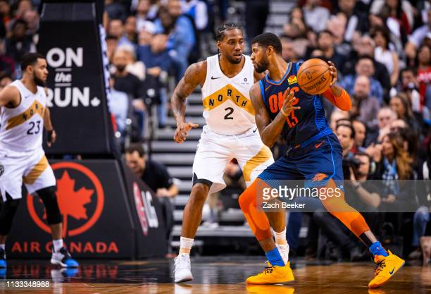 Paul George of the Oklahoma City Thunder handles the ball against Kawhi Leonard of the Toronto Raptors on March 22 2019 at Scotiabank Arena in...