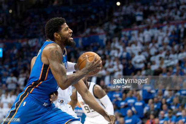 Paul George of the Oklahoma City Thunder tries to shoot over Ekpe Udoh of the Utah Jazz during game 5 of the Western Conference playoffs at the...