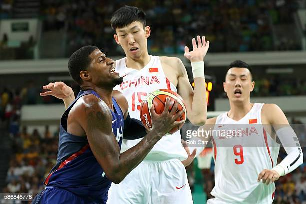 Paul George of United States handles the ball against Qi Zhou and Xiaochuan Zhai of China on Day 1 of the Rio 2016 Olympic Games at Carioca Arena 1...