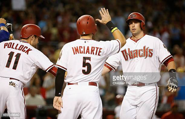 Paul Goldschmidt of the Arizona Diamondbacks high-fives A.J. Pollock and Ender Inciarte at home plate after hitting a three-run home run against the...