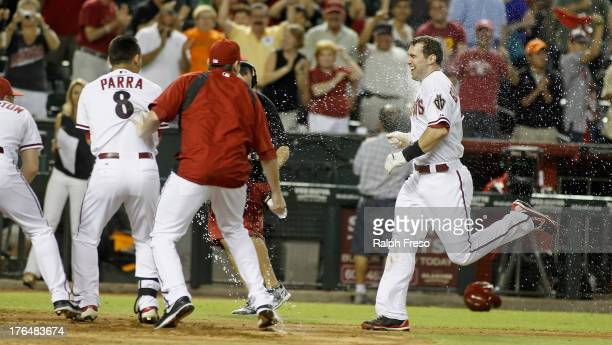 Paul Goldschmidt of the Arizona Diamondbacks is dowsed with water by teammates as he approaches home plate following his game-winning walk off home...