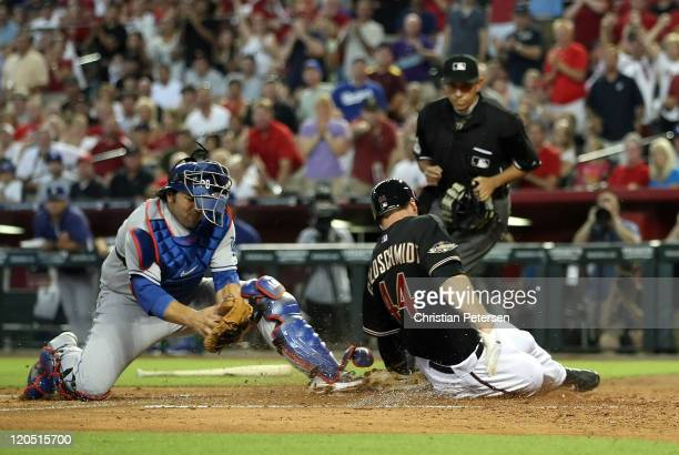 Paul Goldschmidt of the Arizona Diamondbacks safely slides in to score a run past catcher Rod Barajas of the Los Angeles Dodgers during the second...