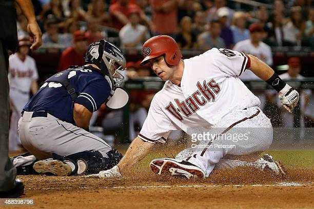 Paul Goldschmidt of the Arizona Diamondbacks safely slides into home plate to score a run past catcher Austin Hedges of the San Diego Padres during...