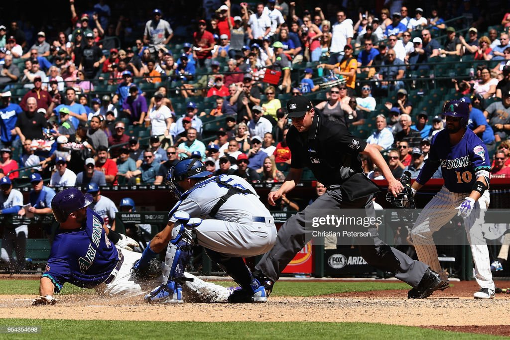 Paul Goldschmidt #44 of the Arizona Diamondbacks safely slides into home plate to score a run past catcher Austin Barnes #15 of the Los Angeles Dodgers during the sixth inning of the MLB game at Chase Field on May 3, 2018 in Phoenix, Arizona.