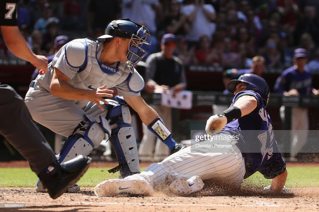 Paul Goldschmidt #44 of the Arizona Diamondbacks safely slides into home plate to score a run past catcher Austin Barnes #15 of the Los Angeles Dodgers during the sixth inning of the MLB game at Chase Field on May 3, 2018 in Phoenix, Arizona. The Dodgers defeated the Diamondbacks 5-2.