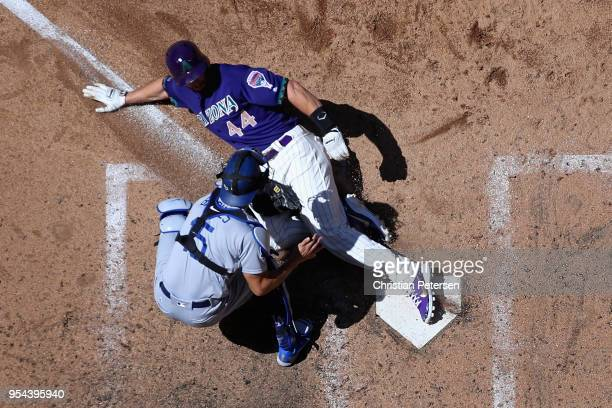 Paul Goldschmidt of the Arizona Diamondbacks safely slides into home plate to score a run past catcher Austin Barnes of the Los Angeles Dodgers...