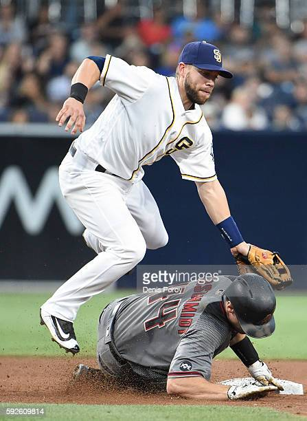 Paul Goldschmidt of the Arizona Diamondbacks slides into second base as Ryan Schimpf of the San Diego Padres loses the ball during the fifth inning...