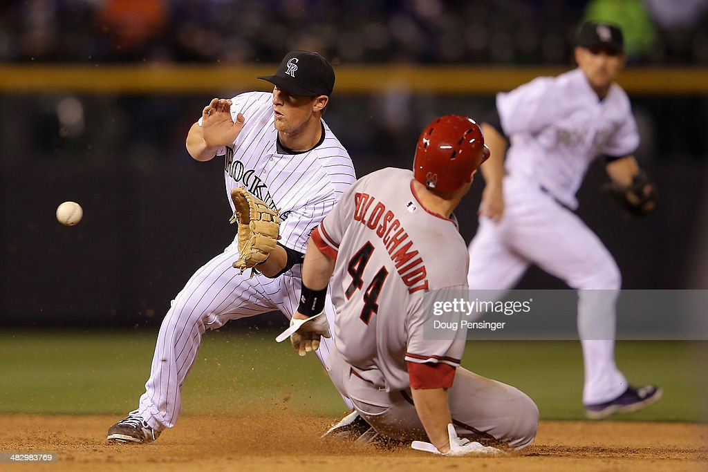 Paul Goldschmidt #44 of the Arizona Diamondbacks slides safely into second with a stolen base as second baseman DJ LeMahieu #9 of the Colorado Rockies takes the late throw in the fifth inning at Coors Field on April 5, 2014 in Denver, Colorado.