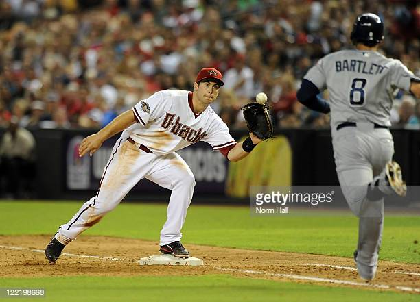 Paul Goldschmidt of the Arizona Diamondbacks watches the ball into his glove as Jason Bartlett of the San Diego Padres hustles down the first base...