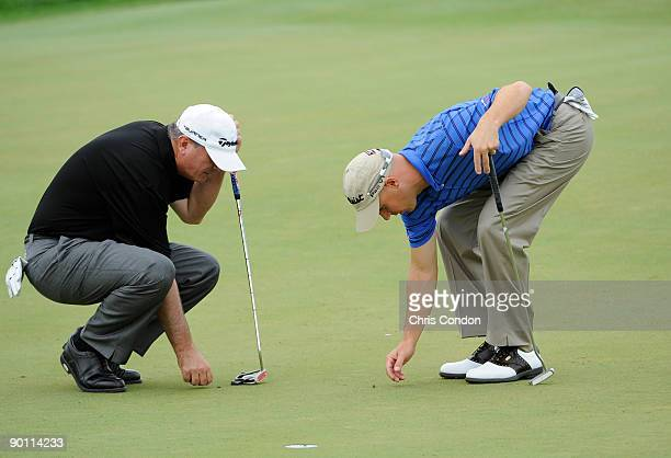 Paul Goydos and Ben Crane look at spike marks on the third green on during the first round of The Barclays at Liberty National Golf Club on August 27...