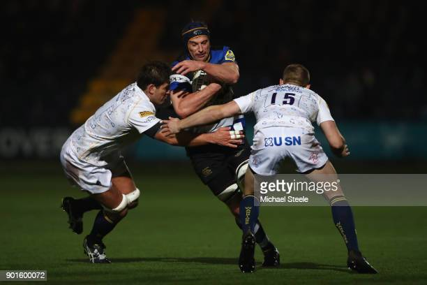 Paul Grant of Bath is tackled by Donncha O'Callaghan and Chris Pennell of Worcester during the Aviva Premiership match between Worcester Warriors and...