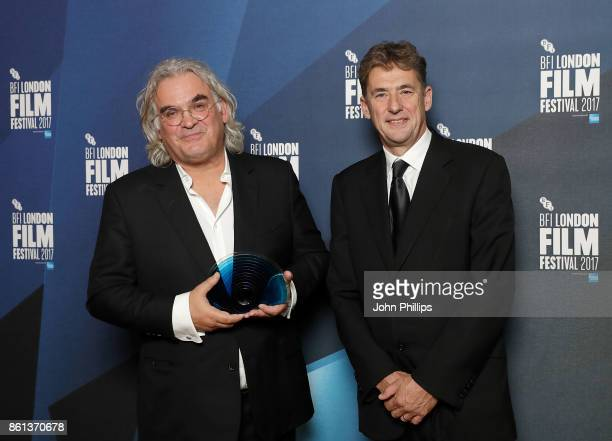 Paul Greengrass poses in the winners room with his BFI Fellowship award and award presenter Tim Bevan at the 61st BFI London Film Festival Awards on...