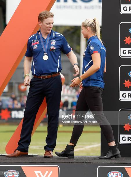 Paul Groves Senior Coach of the Bulldogs welcomes suspended captain Katie Brennan of the Bulldogs to the stage during the 2018 AFLW Grand Final match...