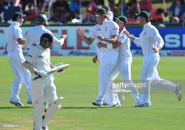 Paul Harris celebrates with South Africa teammates after taking the catch to get the wicket of Gautam Gambhir of India for 5 runs off Morne Morkel of...