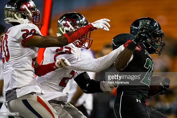 Paul Harris of the Hawaii Warriors is forced out of bounds by Malcolm Washington and Alan Wright of the Fresno State Bulldogs during the second half...
