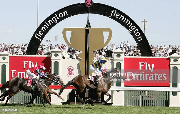 Paul Harvey riding Plastered celebrates as he crosses the winning post during the AAMI Victoria Derby Day at Flemington Racecourse October 30 2004 in...