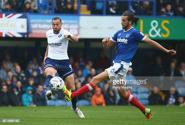 Paul Hayes of Wycombe Wanderers scores his second goal despite the challenge from Christian Burgess of Portsmouth during the Sky Bet League Two match...
