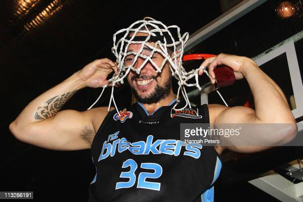 Paul Henare of the Breakers cuts down the net after winning game three of the NBL Grand Final series between the New Zealand Breakers and the Cairns...