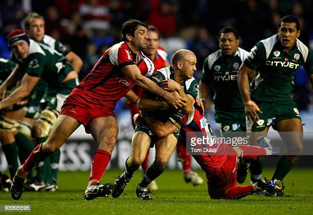 Paul Hodgson of London Irish is tackled by Pat Sanderson and Jonny Arr of Worcester Warriors during the Guinness Premiership match between London...