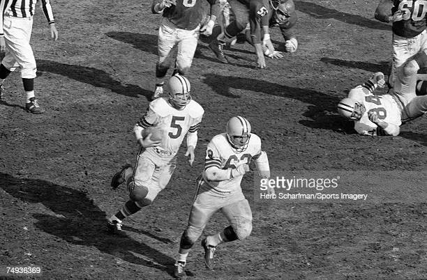 Paul Hornung of the Green Bay Packers carries the ball as Fred Thurston of the Green Bay Packers blocks for him against the Philadelphia Eagles in...