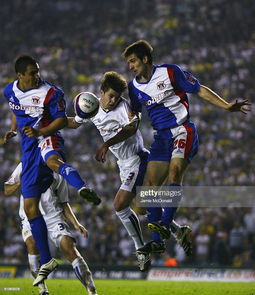 Paul Huntington of Leeds heads the ball between Scott Dobie and Evan Horwood of Carlisle during the League 1 Playoff Semi Final, 1st Leg match between Leeds United and Carlisle United at Elland Road on May 12, 2008 in Leeds, England.