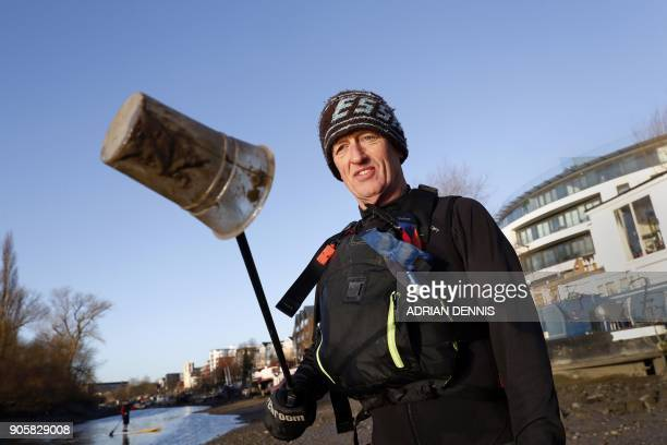 Paul Hyman holds up a plastic cup with a litter picker during a collection of discarded plastic and rubbish from the banks of the River Thames near...