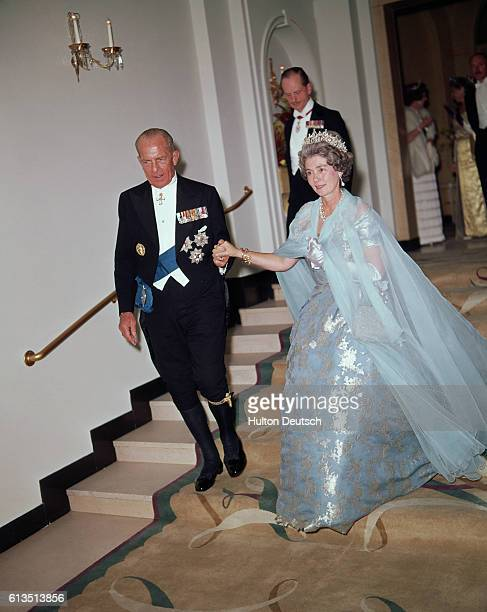 Paul I King of the Hellenic Republic of Greece escorts his wife Queen Fredericka as they descend a flight of steps