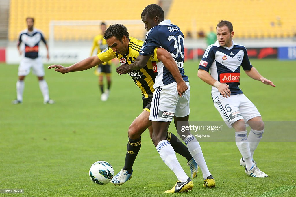 Paul Ifill of the Phoenix is tackled by Jason Geria of the Victory during the round 27 A-League match between the Wellington Phoenix the Melbourne Victory at Westpac Stadium on March 31, 2013 in Wellington, New Zealand.