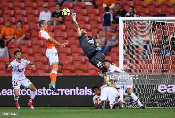 Paul Izzo of Adelaide United punches the ball away ahead of Luke De Vere of the Roar during the round two ALeague match between the Brisbane Roar and...
