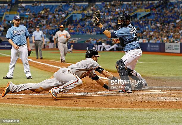 Paul Janish of the Baltimore Orioles slides home ahead of catcher JP Arencibia of the Tampa Bay Rays to score off of an RBI single by Gerardo Parra...