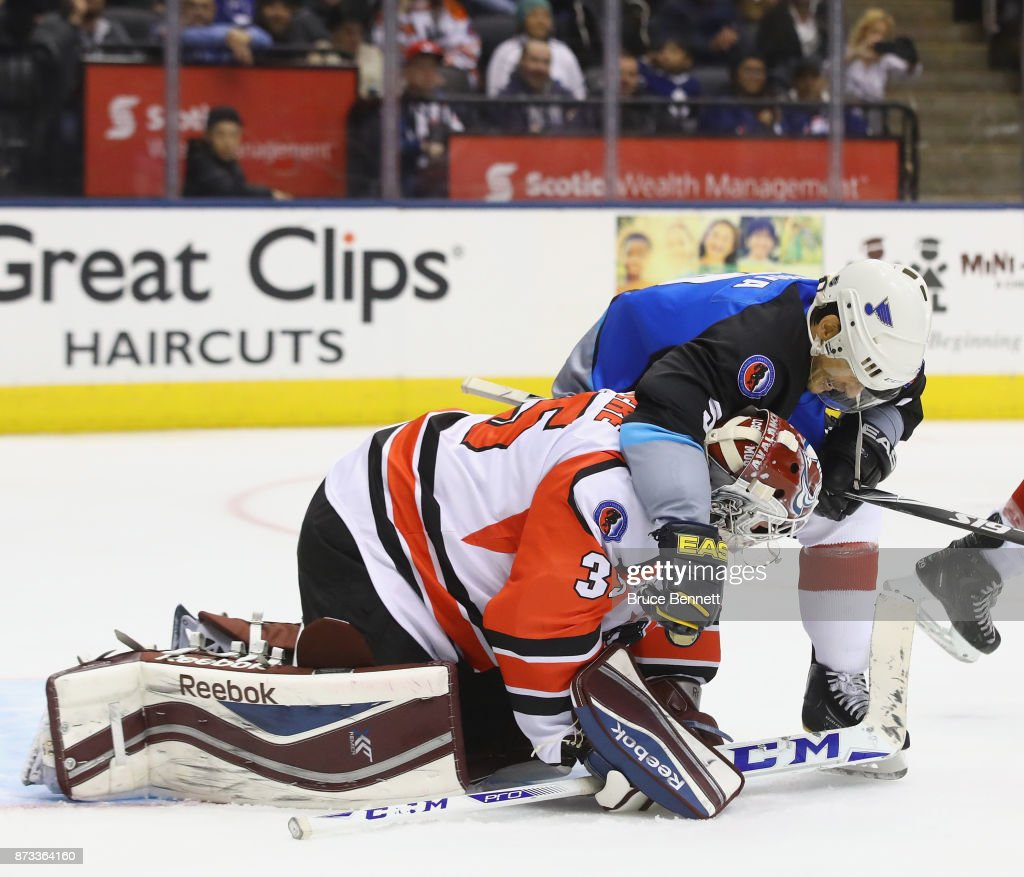 Paul Kariya #9 grabs J.S. Giguere following a save during the Legends Classic game at the Air Canada Centre on November 12, 2017 in Toronto, Canada. Both players played for the Anaheim Ducks and Kariya is set to be inducted into the Hockey Hall of Fame on Monday.