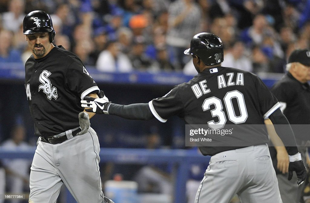 Paul Konerko #14 and Alejandro De Aza #30 of the Chicago White Sox celebrate a ninth-inning run during MLB-game action against the Toronto Blue Jays April 16, 2013 at Rogers Centre in Toronto, Ontario, Canada.